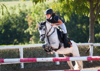 Young girl with roan pony upon hurdle on showjumping competition